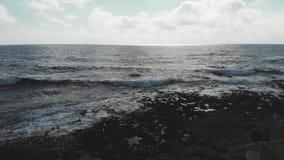 女性黑暗的剪影有胳膊的大开在站立在与击中海洋海滩的强的波浪的峭壁的空气 r 股票录像