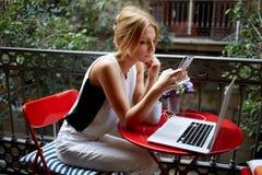 女性读书某事在巧妙的电话,当等待对在她的网书时的被下载的录影 库存图片