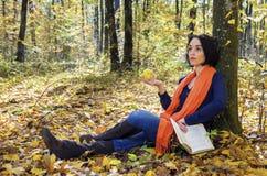 女性读书科学书在森林里 免版税图库摄影