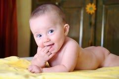女性婴孩咬住在一块黄色毛巾的手 免版税库存照片