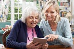 女性邻居显示资深妇女如何使用数字式片剂 免版税库存图片