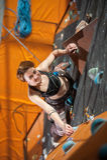 女性登山人在室内攀岩墙壁上爬上 免版税库存图片