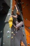 女性登山人在室内攀岩墙壁上爬上 库存图片