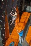 女性登山人在室内攀岩墙壁上爬上 库存照片