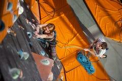 女性登山人在室内攀岩墙壁上爬上 图库摄影