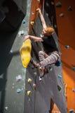 女性登山人在室内攀岩墙壁上爬上 免版税库存照片