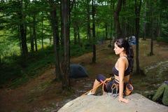 女性登山人坐大自然冰砾在森林里 免版税库存照片