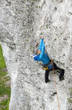 女性登山人,攀登垂直的岩石的妇女 免版税图库摄影