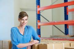 女性仓库工作者微笑的微笑与箱子和包裹户内 免版税库存图片