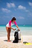 女性轻潜水员检查她的设备 库存图片