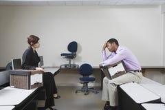 女性经理和沮丧的人坐书桌 免版税库存照片