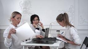 女性医生与文件和X-射线照片一起使用在医疗办公室