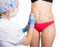 女性医生在脂肪团更正的女性身体做虚线 整容外科 举和乳房 免版税库存照片