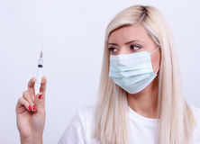 女性医生或护士拿着注射器有inje的医疗面具的 免版税库存图片