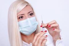 女性医生或护士拿着注射器有inje的医疗面具的 免版税图库摄影
