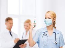 女性医生或护士拿着注射器的面具的 免版税图库摄影