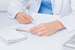 女性医生文字处方在桌上 免版税库存图片