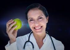 女性医生用反对蓝色火光的苹果 免版税库存照片