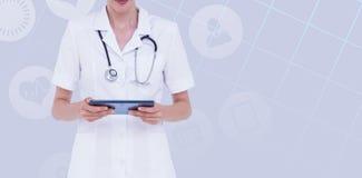 女性医生的中央部位的综合图象使用片剂计算机的 免版税库存图片