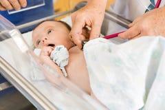 女性医生的Hands Examining Newborn Babygirl 免版税库存图片