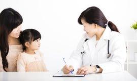 女性医生谈话与孩子和母亲 免版税图库摄影