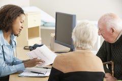 年轻女性医生谈话与资深夫妇 免版税图库摄影