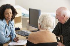 年轻女性医生谈话与资深夫妇 库存图片