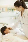 女性医生谈话与躺下在医院病床上的女孩患者 库存图片
