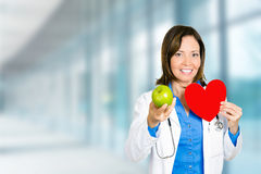 女性医生医疗保健专家用红色心脏绿色苹果 免版税库存照片