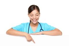 年轻女性医生Pointing At Copyspace 免版税库存图片