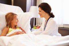 女性医生Talking To Child Patient在医院病床上 库存图片