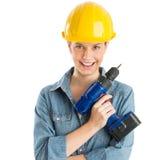 女性建筑工人佩带的盔甲,当拿着钻子时 免版税库存照片