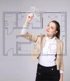 女性建筑师与一个真正公寓计划一起使用 库存照片
