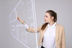 女性建筑师与一个真正公寓计划一起使用 免版税库存图片