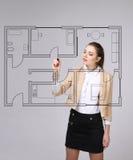 女性建筑师与一个真正公寓计划一起使用 库存图片