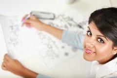女性建筑师与图纸一起使用在办公室 免版税图库摄影