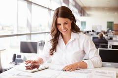 女性建筑师在工作在使用片剂计算机的一个办公室 库存照片