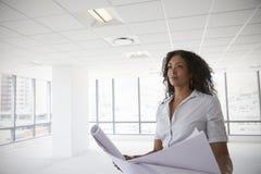 女性建筑师在看计划的现代空的办公室 免版税图库摄影