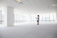 女性建筑师在看计划的现代空的办公室 免版税库存图片