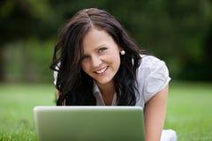女性说谎在使用膝上型计算机的草 库存照片