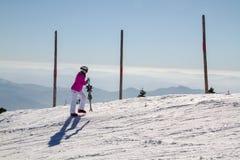 女性滑雪者在山顶部 免版税库存图片