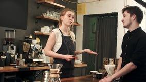 女性barista谈话与咖啡馆的顾客,接受命令 免版税库存图片