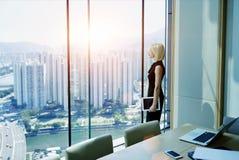 女性CEO在现代办公室内部近的窗口里站立有都市风景视图 免版税图库摄影
