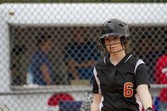 女性Fastpitch垒球运动员标题到估量投手的击球员区里 免版税图库摄影