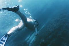 女性freediver游泳在深海 免版税库存照片