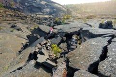 年轻女性Kilauea Iki火山火山口的游人探索的表面与粉碎的熔岩岩石的在双的火山国家公园 库存图片