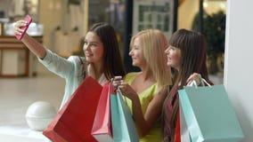 女性shopaholism,快乐的女朋友在手上拍在手机的照片,当购物与包裹在销售期间时 股票录像