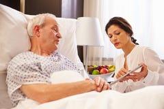 女性Talking To Senior Male医生患者在医院病床上 免版税库存图片