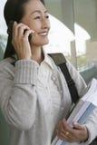 女性Using Cellphone While Holding教授书 免版税库存图片