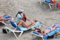 女按摩师做在海滩的按摩 库存图片